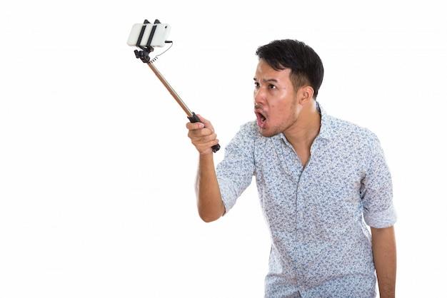 Giovane uomo asiatico arrabbiato che prende l'immagine del selfie con il telefono cellulare