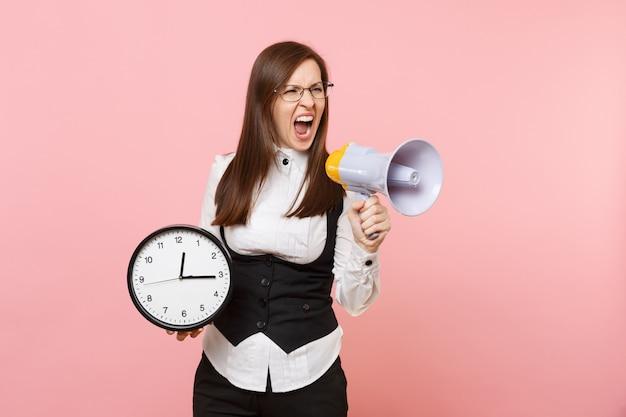 Giovane donna d'affari arrabbiata in tuta, occhiali che urlano con megafono e sveglia isolati su sfondo rosa pastello. signora capo. concetto di ricchezza di carriera di successo. copia spazio per la pubblicità.