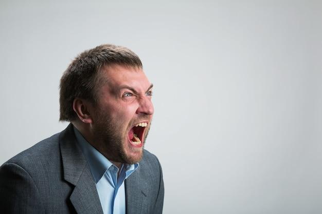 Giovane uomo d'affari arrabbiato che grida sopra gray