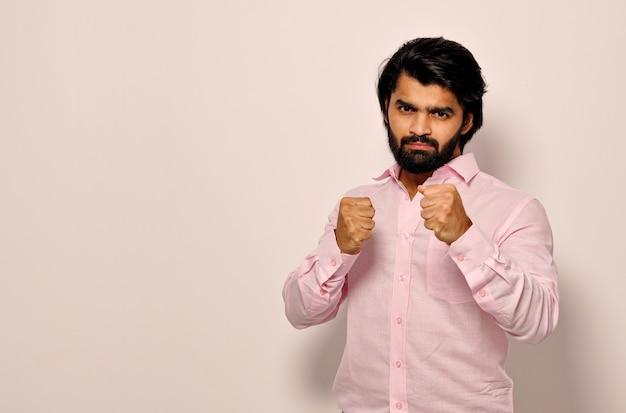 Giovane uomo arrabbiato pronto a combattere in posizione di boxe