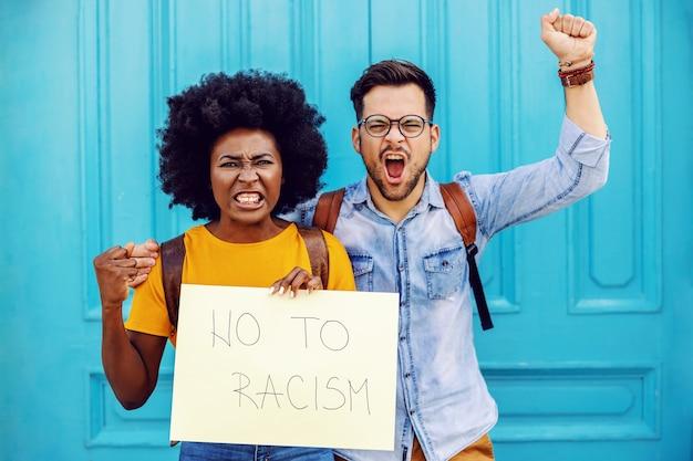 Giovani coppie multiculturali arrabbiate che gridano e che tengono carta con il titolo di no al razzismo