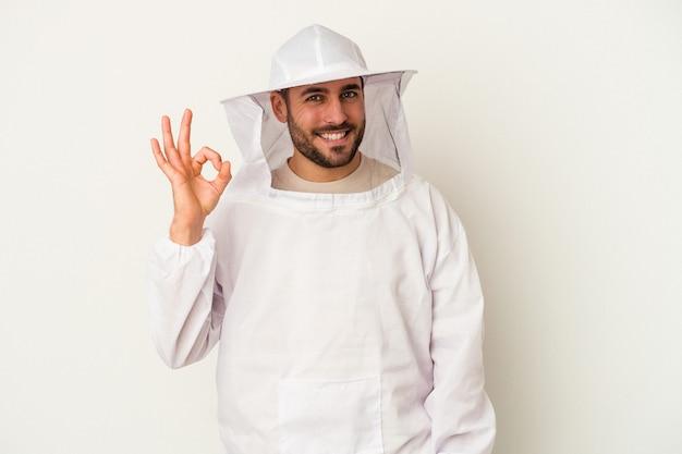 Giovane uomo caucasico di apicoltura isolato su sfondo bianco allegro e fiducioso che mostra gesto giusto.