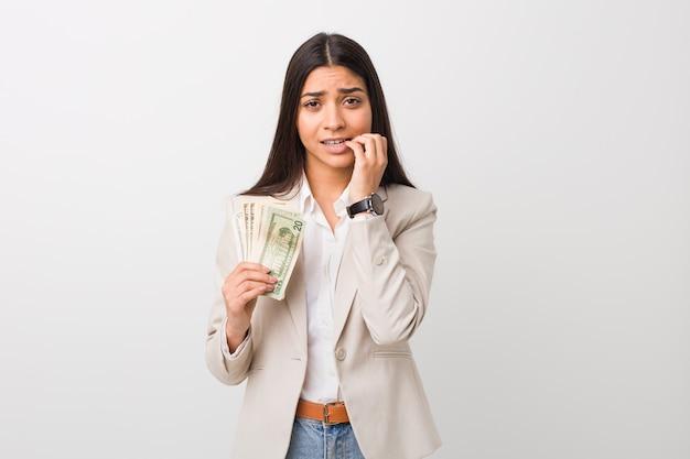 Giovane donna araba di affari che tiene i dollari che morde le unghie, nervosa e molto ansiosa.