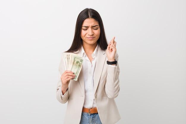 Giovane donna araba di affari che tiene i dollari che attraversano le dita per avere fortuna