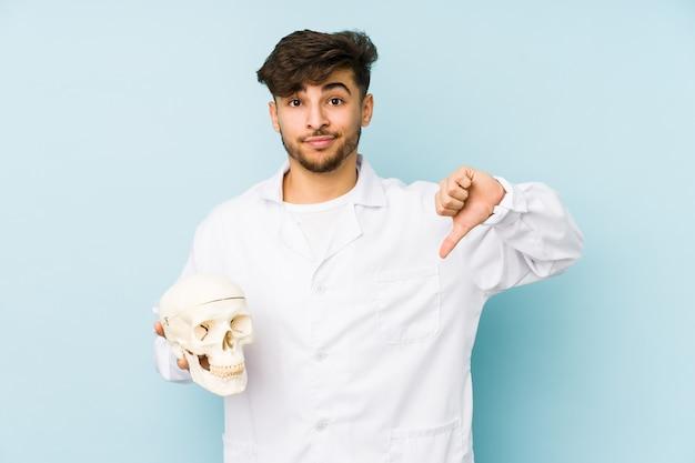 Giovane uomo arabo del medico che tiene un cranio che mostra un gesto di antipatia, pollici giù
