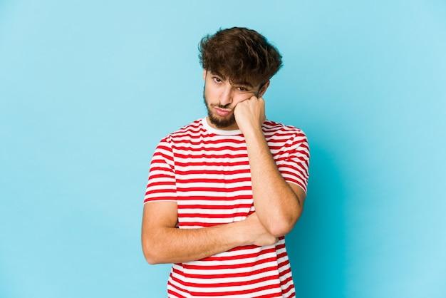 Giovane uomo arabo su sfondo blu che si sente triste e pensieroso, guardando lo spazio della copia.