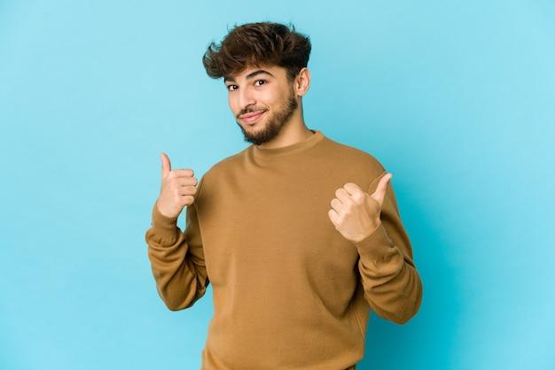 Giovane uomo arabo sull'azzurro che alza entrambi i pollici in su, sorridente e sicuro.