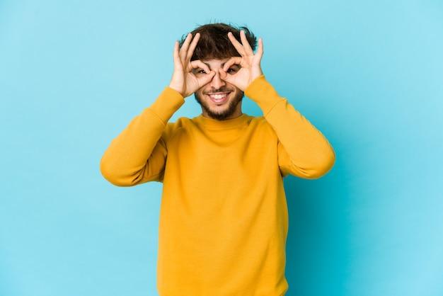Giovane uomo arabo sull'azzurro che mostra segno giusto sopra gli occhi