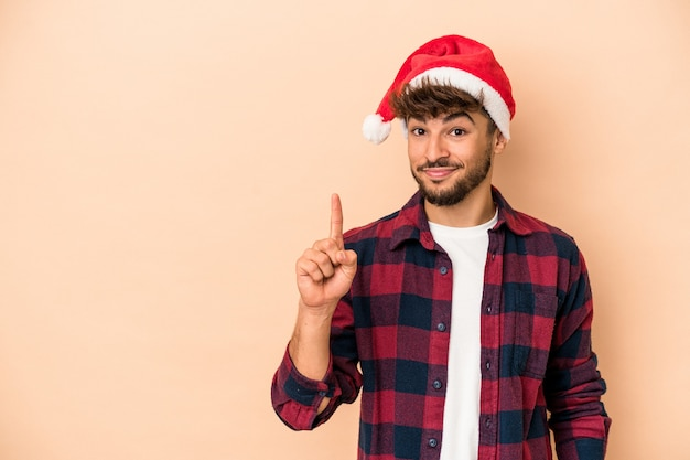 Giovane uomo arabo che celebra il natale isolato su sfondo beige che mostra il numero uno con il dito.