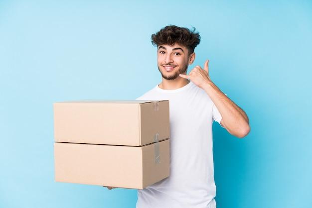 Giovane uomo arabo che tiene le scatole isolate che mostra un gesto di chiamata di telefono cellulare con le dita.