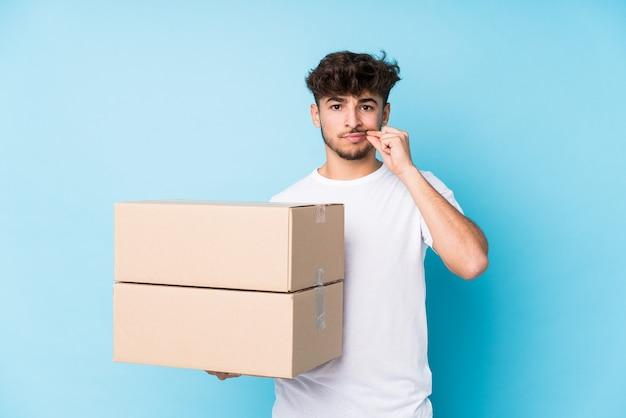 Giovane uomo arabo che tiene le scatole isolate con le dita sulle labbra mantenendo un segreto