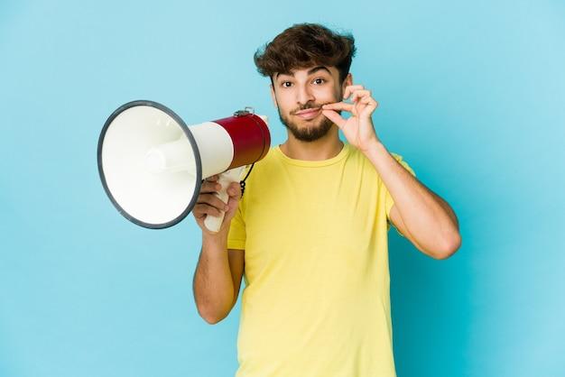Giovane uomo arabo che tiene un megafono con le dita sulle labbra mantenendo un segreto.