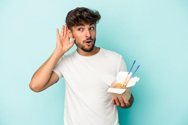 Giovane uomo arabo tenendo un take away noodles isolati su sfondo blu cercando di ascoltare un pettegolezzo.