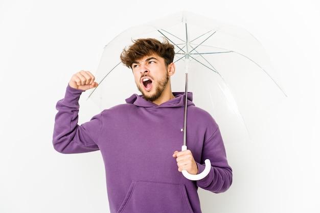 Giovane uomo arabo che tiene un ombrello che alza il pugno dopo una vittoria, concetto del vincitore.