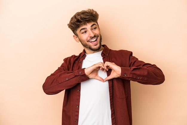 Giovane uomo arabo isolato su fondo beige che sorride e che mostra una forma del cuore con le mani.