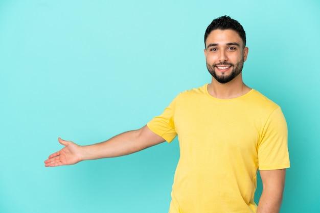 Giovane uomo arabo isolato su sfondo blu che allunga le mani di lato per invitare a venire