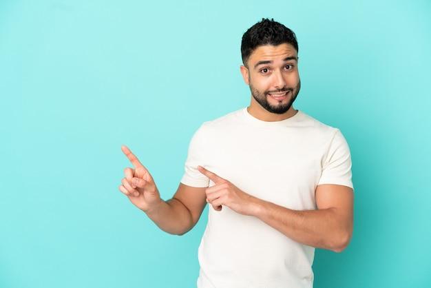 Giovane uomo arabo isolato su sfondo blu spaventato e indicando il lato