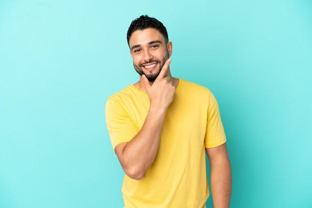 Giovane uomo arabo isolato su sfondo blu felice e sorridente