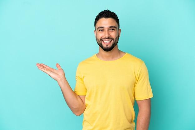 Giovane uomo arabo isolato su sfondo blu che tiene copyspace immaginario sul palmo per inserire un annuncio