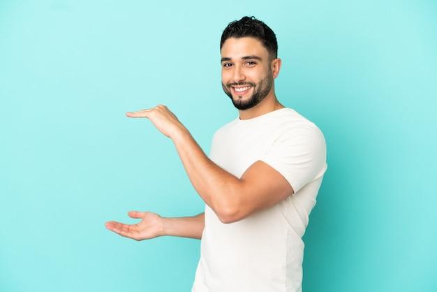 Giovane uomo arabo isolato su sfondo blu tenendo copyspace per inserire un annuncio