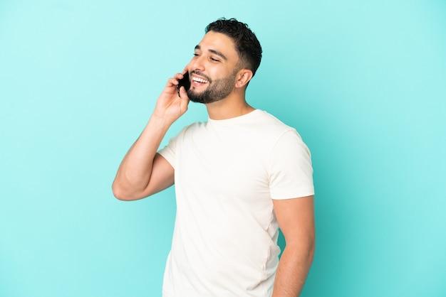 Giovane uomo arabo isolato su sfondo blu che tiene una conversazione con il telefono cellulare