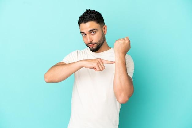 Giovane uomo arabo isolato su sfondo blu che fa il gesto di essere in ritardo