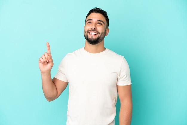 Giovane uomo arabo isolato su sfondo blu rivolto verso l'alto e sorpreso