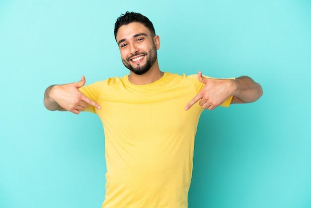 Giovane uomo arabo isolato su sfondo blu orgoglioso e soddisfatto di sé