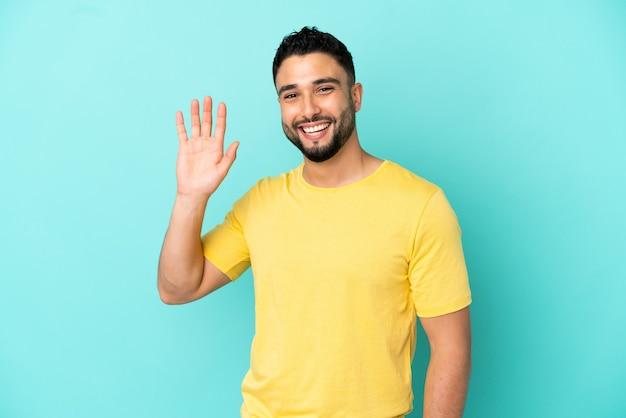 Giovane uomo arabo isolato su sfondo blu che saluta con la mano con espressione felice