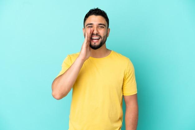 Giovane uomo arabo isolato su sfondo blu che grida con la bocca spalancata