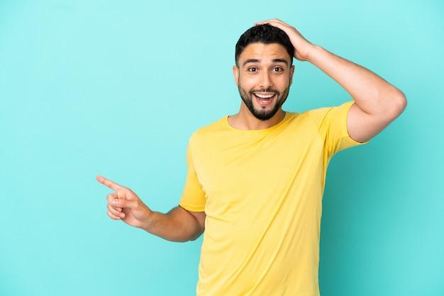 Giovane uomo arabo isolato su sfondo blu sorpreso e puntando il dito di lato