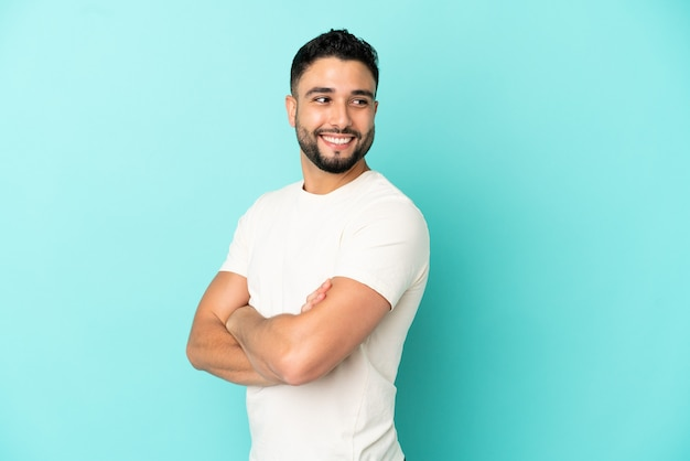 Giovane uomo arabo isolato su sfondo blu con le braccia incrociate e felice