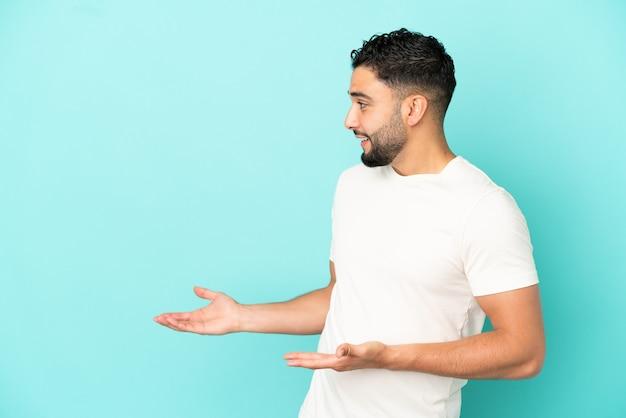 Giovane uomo arabo isolato su sfondo blu con espressione di sorpresa mentre guarda di lato