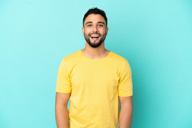 Giovane uomo arabo isolato su sfondo blu con espressione facciale a sorpresa