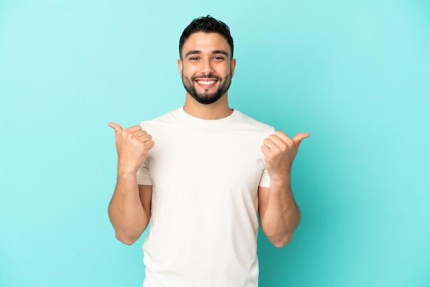 Giovane uomo arabo isolato su sfondo blu con gesto di pollice in alto e sorridente
