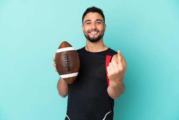 Giovane uomo arabo che gioca a rugby isolato su sfondo blu facendo un gesto imminente