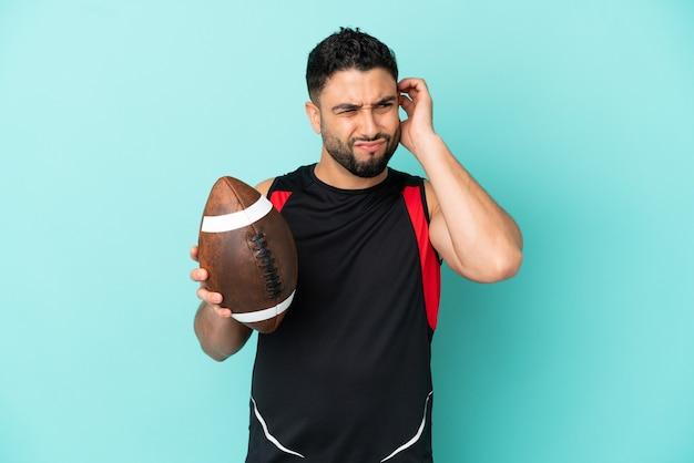 Giovane uomo arabo che gioca a rugby isolato su sfondo blu frustrato e che copre le orecchie