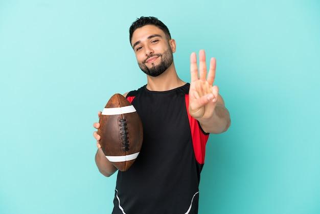 Giovane arabo che gioca a rugby isolato su sfondo blu felice e conta tre con le dita
