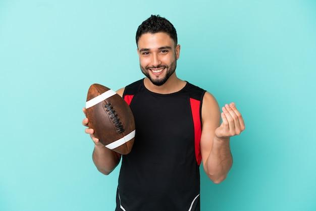 Giovane uomo arabo che gioca a rugby isolato su fondo blu che fa il gesto dei soldi