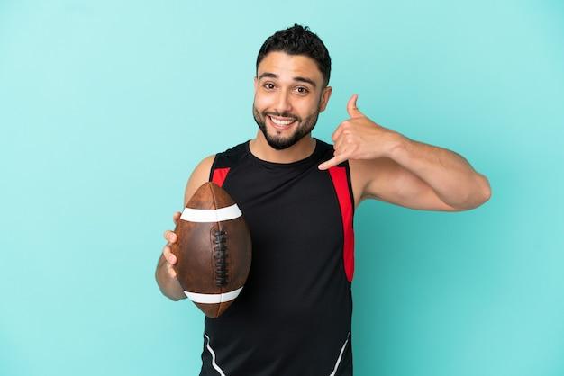 Giovane uomo arabo che gioca a rugby isolato su sfondo blu facendo gesto di telefono. richiamami segno
