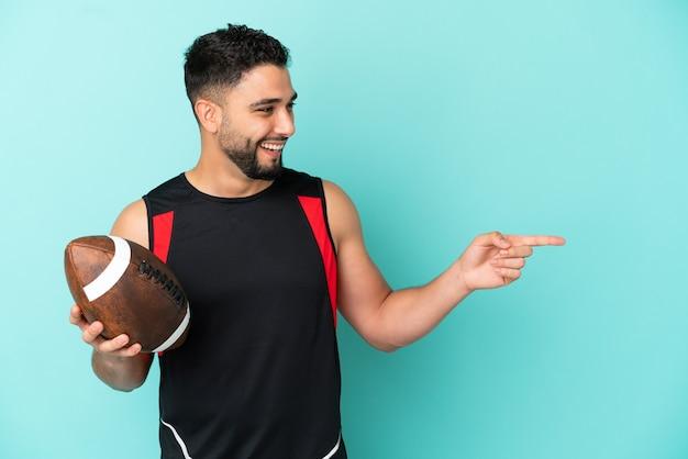 Giovane uomo arabo che gioca a rugby isolato su sfondo blu che punta il dito di lato e presenta un prodotto