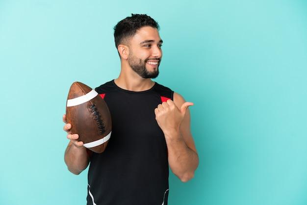 Giovane uomo arabo che gioca a rugby isolato su sfondo blu che punta al lato per presentare un prodotto
