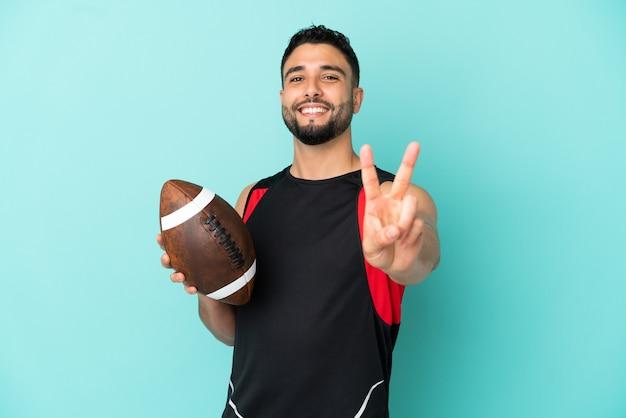 Giovane uomo arabo che gioca a rugby isolato su sfondo blu che sorride e mostra il segno della vittoria