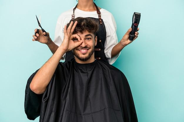Giovane uomo arabo pronto a ottenere un taglio di capelli isolato su sfondo blu eccitato mantenendo il gesto ok sull'occhio.