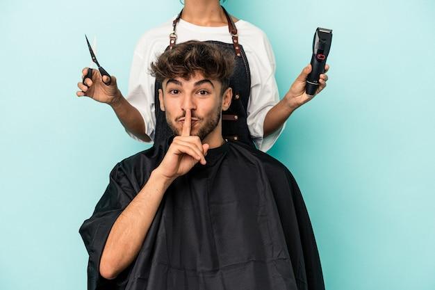 Giovane uomo arabo pronto a farsi tagliare i capelli isolato su sfondo blu mantenendo un segreto o chiedendo silenzio.