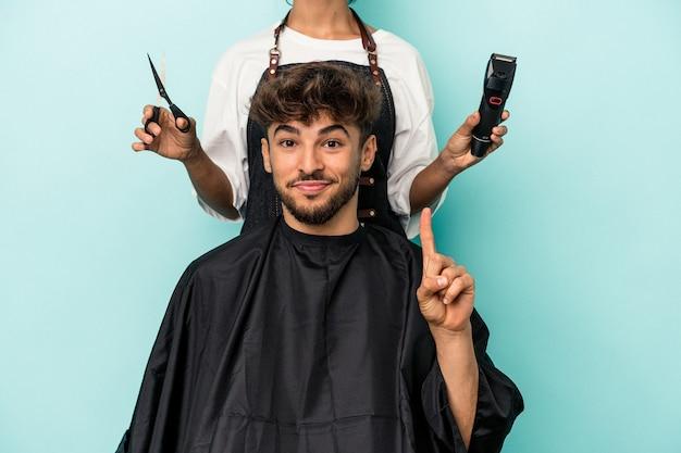 Giovane uomo arabo pronto a ottenere un taglio di capelli isolato su sfondo blu che mostra il numero uno con il dito.