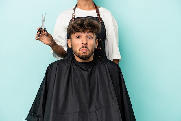 Il giovane arabo pronto a ottenere un taglio di capelli isolato su sfondo blu alza le spalle e apre gli occhi confusi.