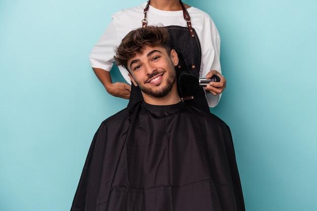 Giovane uomo arabo pronto a farsi tagliare i capelli isolato su sfondo blu