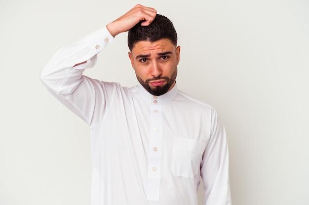 Il giovane arabo che indossa abiti tipici arabi isolati su bianco è scioccato, ha ricordato un incontro importante.