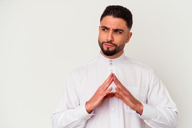Giovane uomo arabo che indossa abiti tipici arabi isolati su bianco che compongono il piano in mente, creando un'idea.